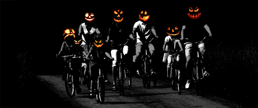 Photo of group of cyclists with Jackolantern heads riding along dark road